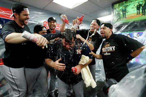 Houston Astros Chris Devenski and James Hoyt spray champagne on bullpen coach Criag Bjornson in the clubhouse after the Astros beat Boston Red Sox 5-4 in the ALDS Game 4 at Fenway Park, Monday, Oct. 9, 2017, in Boston .