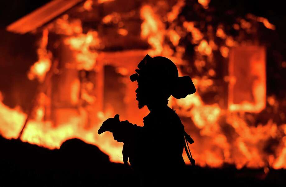 An inmate firefighter monitors flames as a house burns in the Napa wine region in California on Monday. Wind-driven fires continue to whip through the region. Photo: JOSH EDELSON, Contributor / AFP or licensors