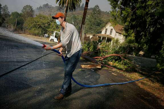 Paolo Solari uses a hose to  put out embers that burn around his  parents home at Solari Vineyards on Monday, October 9, 2017 in Calistoga, Calif.