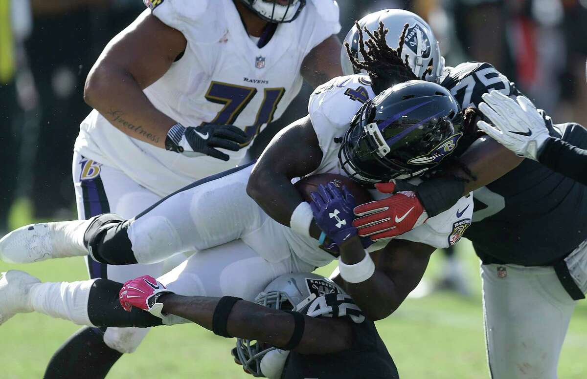 Baltimore Ravens running back Alex Collins, center, is tackled by Oakland Raiders defensive tackle Darius Latham (75) and safety Karl Joseph (42) during the second half of an NFL football game in Oakland, Calif., Sunday, Oct. 8, 2017. (AP Photo/Ben Margot)