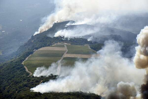 Smoke rise near a vineyard as the Atlas Fire burns in the hills east of Napa, Calif., on Monday, October, 9, 2017.