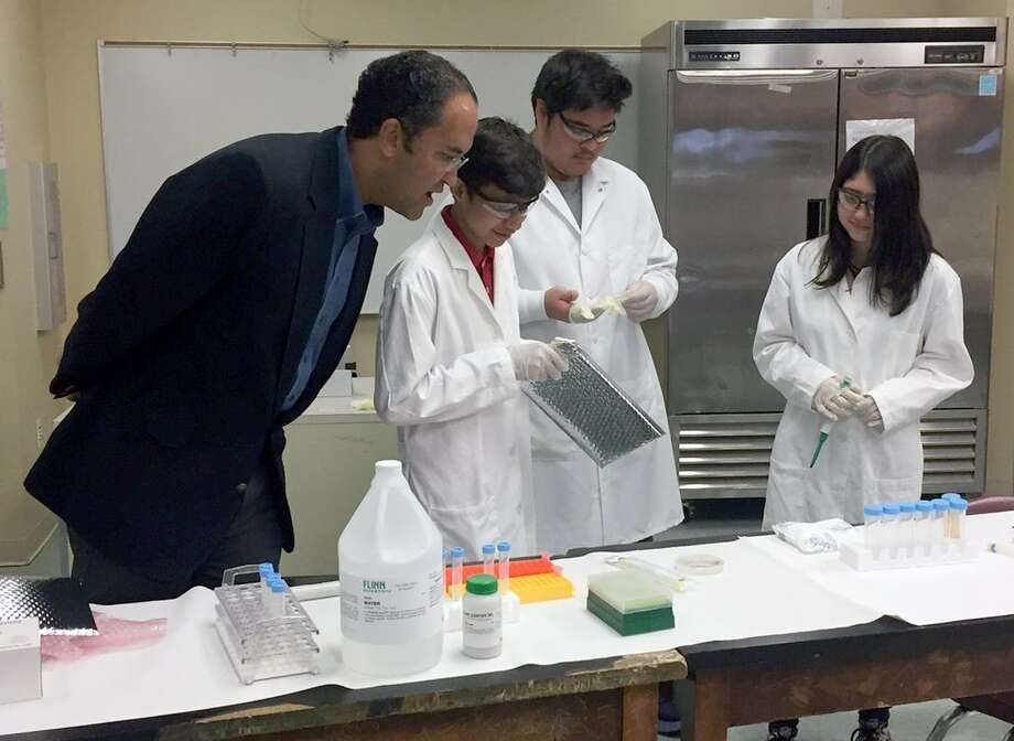 U.S. Rep. Will Hurd, from left, watches Southside High School 9th grade students Carlos Gonzalez, Neco Jimenez and Lydia Araujo as they open the returned experiment they sent to the International Space Station. Photo: Silvia Foster-Frau /SAN ANTONIO EXPRESS-NEWS / SAN ANTONIO EXPRESS-NEWS