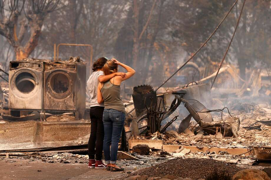 Steph Gediman comforts Brandi Burns on Oct. 9 in front of Burns' Santa Rosa home, destroyed by the Tubbs Fire. Last year saw 16 weather events inflict $1 billion-plus apiece in damage. Photo: Michael Macor, The Chronicle