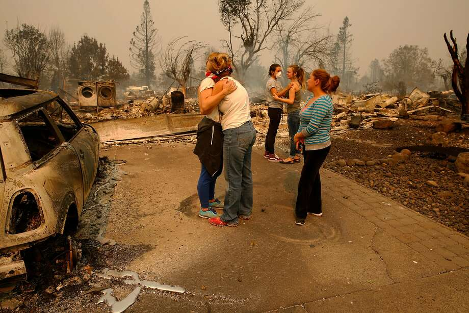 (l to r) Erica Rinkor hugs Terrie Burns, in front of Burns' destroyed home, while Steph Gediman comforts Brandi Burns with Cindy Amador close where dozens of homes burned at the scene of the Tubbs Fire in Santa Rosa, Ca., on Monday October 9, 2017. Massive wildfires ripped through Napa and Sonoma counties early Monday, destroying hundreds of homes and businesses on Monday October 9, 2017 Photo: Michael Macor / The Chronicle 2017