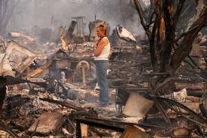 Terrie Burns stands in the middle of her destroyed at the scene of the Tubbs Fire in Santa Rosa, Ca., on Monday October 9, 2017. Massive wildfires ripped through Napa and Sonoma counties early Monday, destroying hundreds of homes and businesses on Monday October 9, 2017