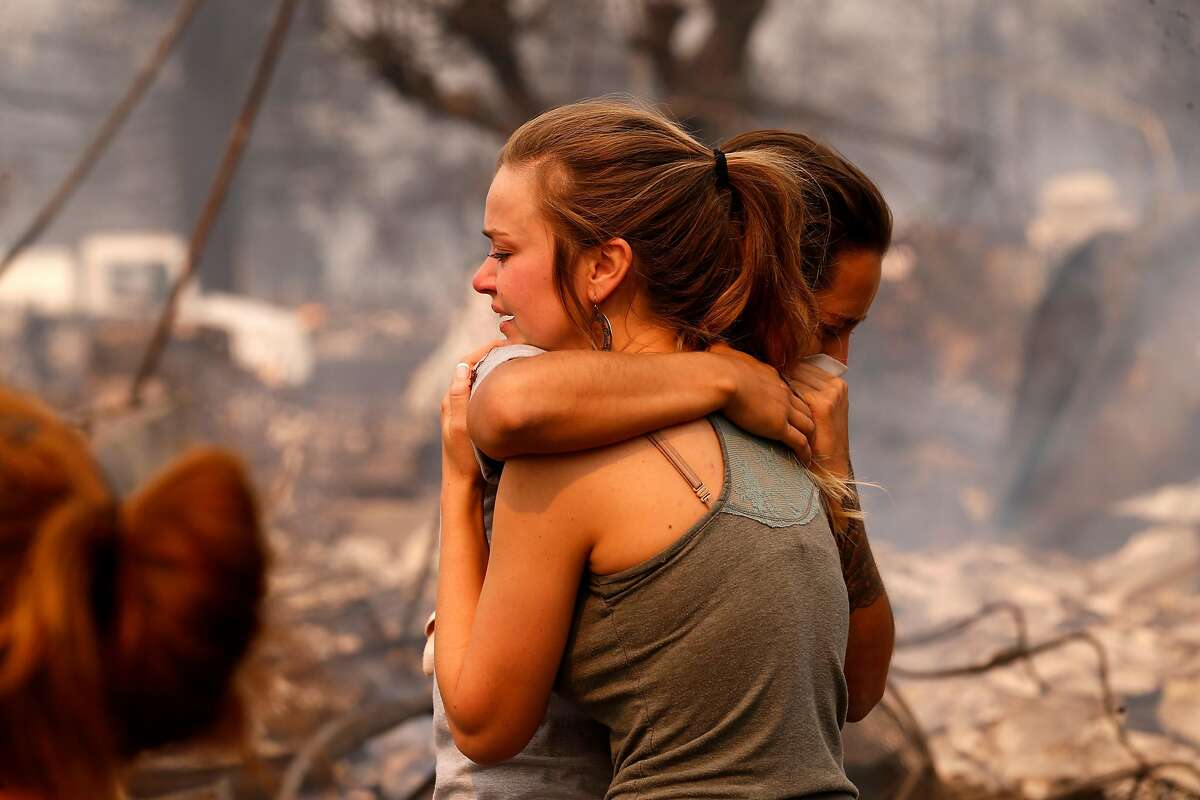 Steph Gediman (foreground) comforts Brandi Burns as they stand in what had been their neighborhood before the Tubbs Fire leveled the swaths of houses in Santa Rosa.