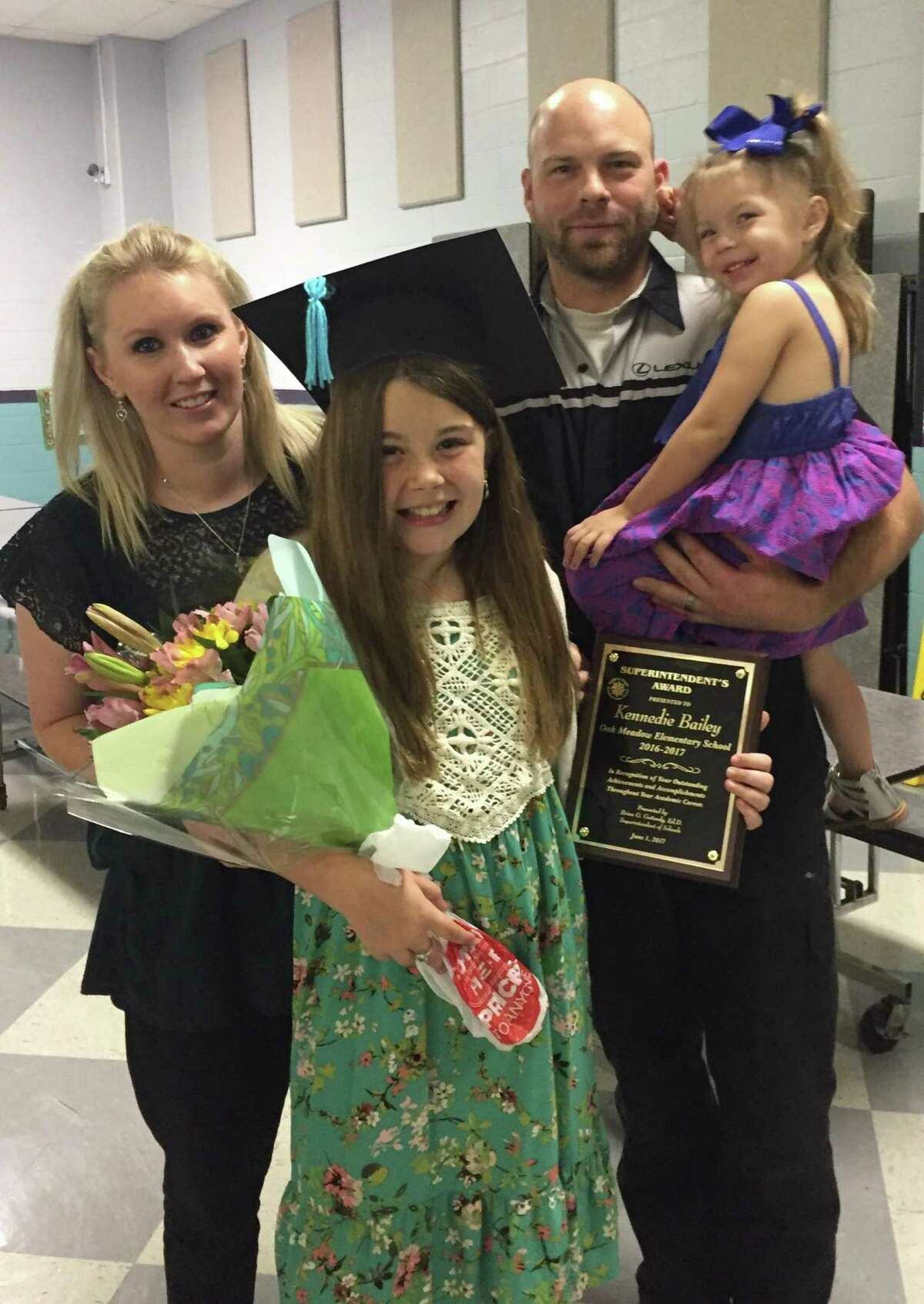 Kennedie Bailey poses with her mother, Lindsey Bendele, her stepfather, Chris Bendele, and her sister, Presley, 4, before starting chemotherapy over the summer. Kennedie was diagnosed with rhabdomyosarcoma, a form of cancer that develops from connective tissues in the body including, muscles, bones, joints and fat.