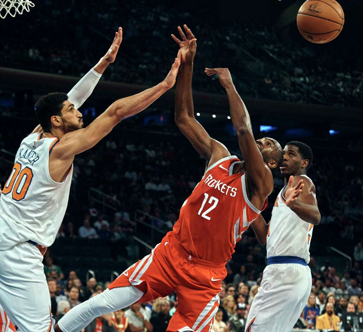 Houston Rockets' Luc Mbah a Moute (12) shoots next to New York Knicks' Enes Kanter (00) during the first half of a preseason NBA basketball game at Madison Square Garden in New York, Monday, Oct. 9, 2017. (AP Photo/Andres Kudacki)