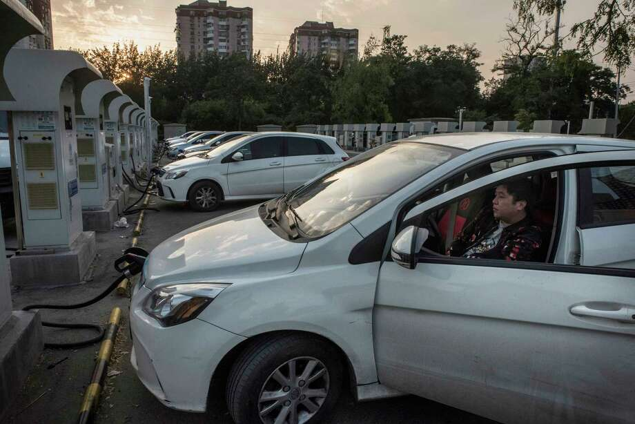 A driver in Beijing waits for his car to charge. Chinese motorists are on course to buy almost 300,000 electric vehicles this year, more than the rest of the world combined.  Photo: GILLES SABRIE, STR / NYTNS