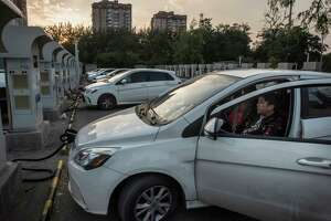 A driver in Beijing waits for his car to charge. Chinese motorists are on course to buy almost 300,000 electric vehicles this year, more than the rest of the world combined. cars, forcing auto makers from Detroit to Seoul to pick up the pace of transformation or risk being left behind. (Gilles Sabrie/The New York Times)