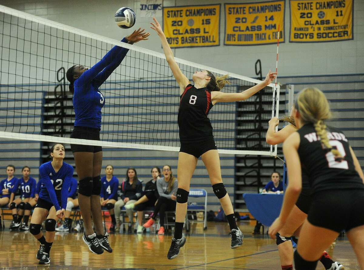 Bunnell's Kayla Sokunle, left, and Warde's Clare Sullivan converge on the ball at the net during Monday's game in Stratford.