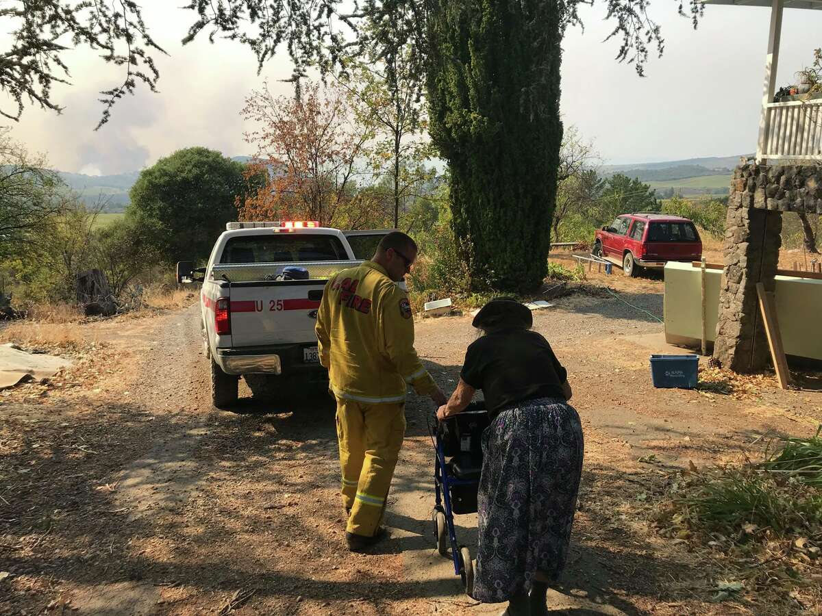 CHP personnel assist an elderly woman and help her to evacuate her home in rural Napa County on Monday, October 9, 2017. Wildfires have ravaged the area.