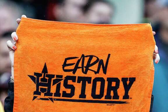 "A Houston Astros fan holds up an ""Earn History"" towel during the ninth inning of Game 4 of the ALDS against the Boston Red Sox at Fenway Park on Monday, Oct. 9, 2017, in Boston. ( Karen Warren / Houston Chronicle )"