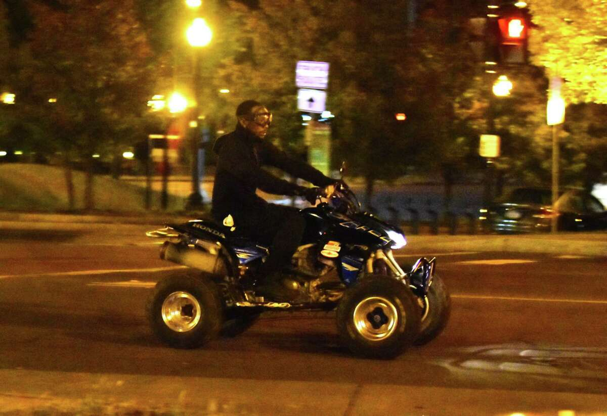 A man rides a quad bike near the Palace Theatre in downtown Albany on Sunday. Police in Albany say people riding non-licensed off-road vehicles on city streets is a problem that has ebbed and flowed over the years. (Steve Barnes/Times Union)