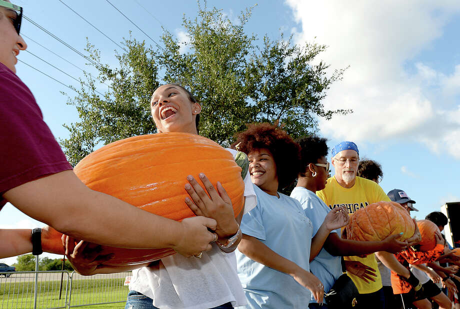 Ivyanna Lewis passes off a heavy pumpkin as she and fellow volunteers form an assembly line to unload thousands of pumpkins and gourds that arrived by truck for Wesley United Methodist Church's annual pumpkin patch. After a delay in transport, the shipment arrived Monday, in time for the church's planned Tuesday pumpkin patch opening from 2 - 5 p.m. The patch will be open for picking, as well as offering family friendly activities, Saturdays 9 - 8 p.m. and Sundays noon - 8 p.m.  Photo taken Monday, October 9, 2017 Kim Brent/The Enterprise Photo: Kim Brent / BEN