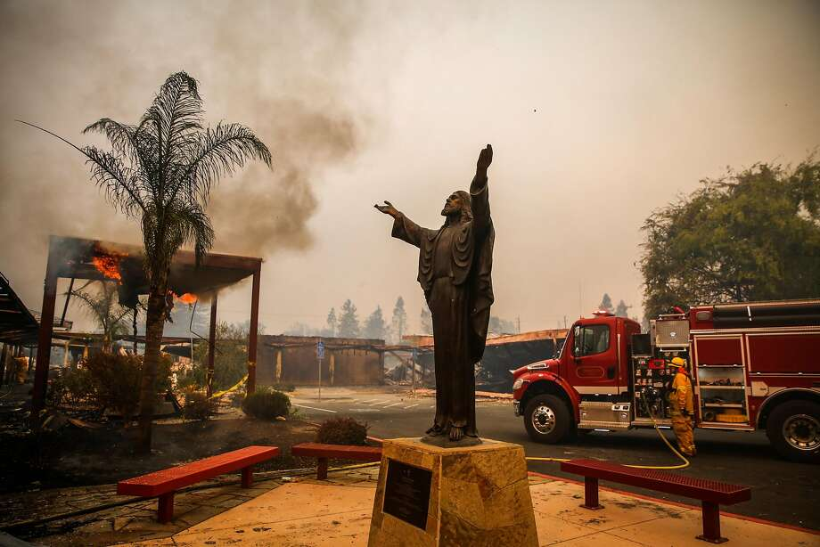 A statue of Jesus is seen while firefighters work to contain the Tubbs fire at Cardinal Newman High School in Santa Rosa, Calif., on Monday, Oct. 9, 2017. Photo: Gabrielle Lurie, The Chronicle