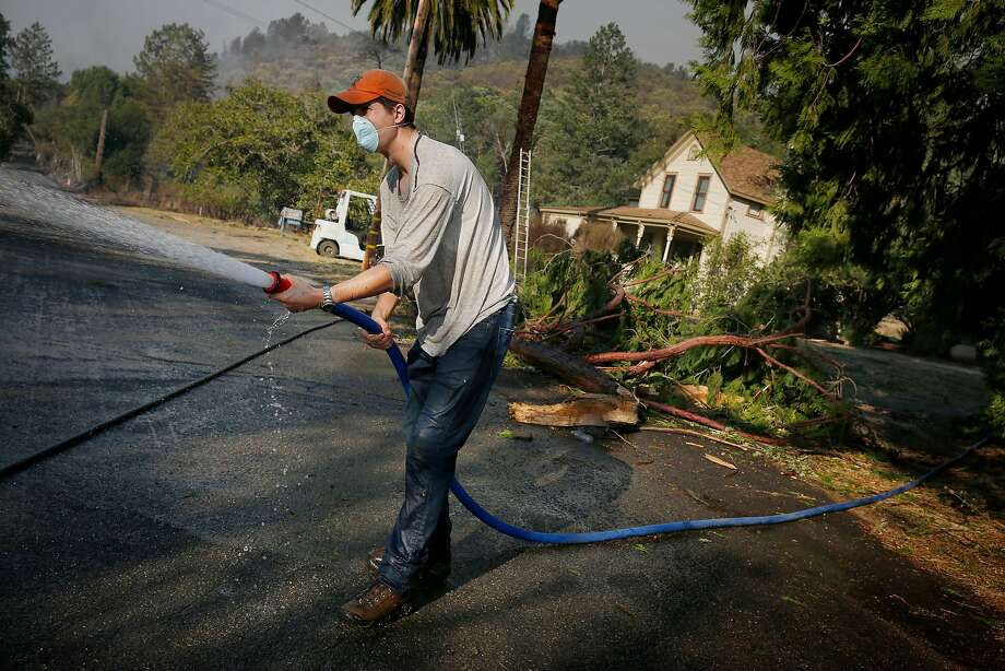 Paolo Solari uses a hose to  put out embers that burn around his  parents home at Solari Vineyards on Monday, October 9, 2017 in Calistoga, Calif. Photo: Lea Suzuki, The Chronicle