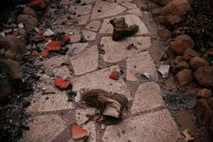 An abandoned pair of boots lay outside a destroyed home off Soda Canyon Road Oct. 9, 2017 in Napa, Calif. A fire tore through the area on the evening of Oct. 8, destroying properties and vineyards.