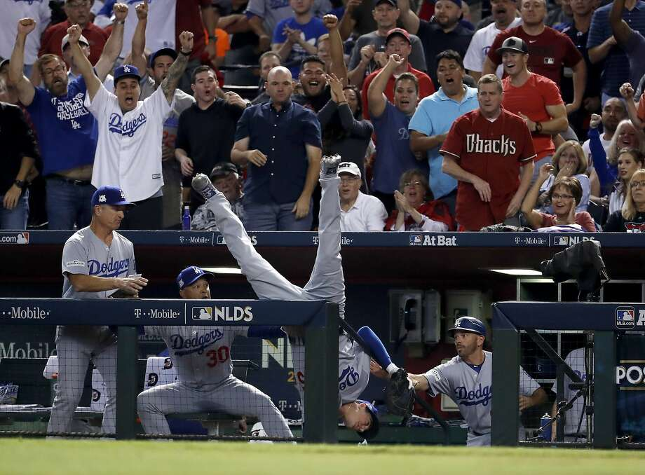 Dodgers first baseman Cody Bellinger flips over the dugout railing after catching Jeff Mathis' foul ball in the fifth inning. Photo: Rick Scuteri, Associated Press