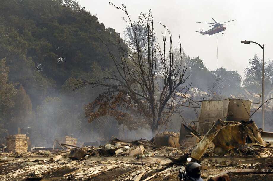A helicopter drops water in the Fountaingrove area on Monday, Oct. 9, 2017, in Santa Rosa, Calif. Wildfires whipped by powerful winds swept through Northern California early Monday, sending residents on a headlong flight to safety through smoke and flames as homes burned. Photo: Ben Margot, Associated Press