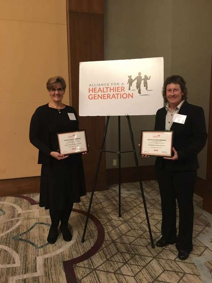 Physical education teachers Jackie Caver from Turner Elementary School, left, and Kathy Byrd from Red Bluff Elementary School accept awards for their campuses from the Alliance for a Healthier Generation.