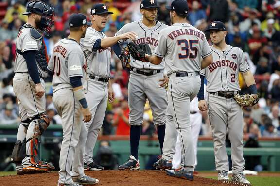 Houston Astros manager A.J. Hinch, third from left, gives the ball to pitcher Justin Verlander (35) for his very first Major League relief appearance during the fifth inning in Game 4 of baseball's American League Division Series against the Boston Red Sox, Monday, Oct. 9, 2017, in Boston. (AP Photo/Michael Dwyer)