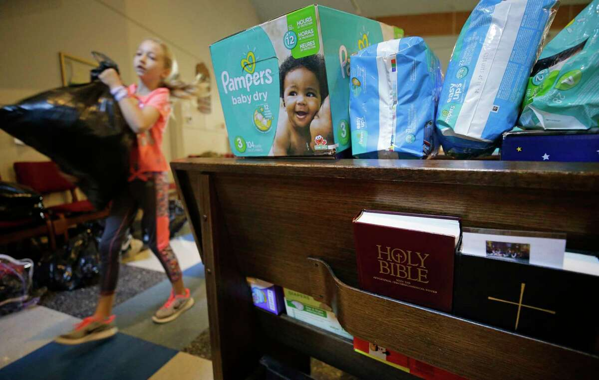 Mackenzie Breeding, 9, of Tomball carries a bag of clothing past pews filled with diapers, as volunteers organize donations at St. Mary's Episcopal Church, 15415 N. Eldridge, Wednesday, August 30, 2017 in Cypress. More than 120 people were temporarily sheltered at the church during flooding. There is an outpouring of donations after Hurricane Harvey. ( Melissa Phillip / Houston Chronicle)