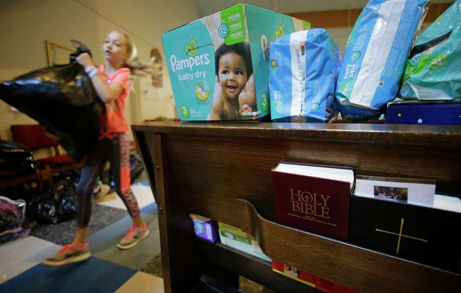 Mackenzie Breeding, 9, of Tomball carries a bag of clothing past pews filled with diapers, as volunteers organize donations at St. Mary's Episcopal Church, 15415 N. Eldridge, Wednesday, August 30, 2017 in Cypress. More than 120 people were temporarily sheltered at the church during flooding. There is an outpouring of donations after Hurricane Harvey. ( Melissa Phillip / Houston Chronicle) Photo: Melissa Phillip, Staff / Internal