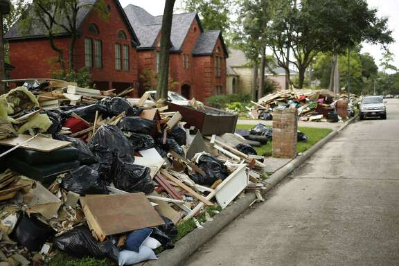 Debris sits in piles outside homes flooded after Hurricane Harvey in Spring, Texas, U.S., on Wednesday, Sept. 6, 2017. Disaster is fueling a growth industry as more frequent and powerful storms lash coastal regions teeming with new homes and offices. Photographer: Luke Sharrett/Bloomberg