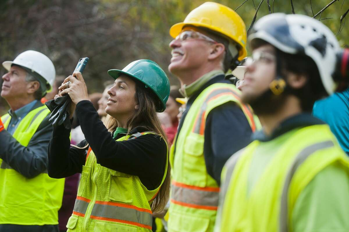 Abbey Claerhout, a horticulturist with Dow Gardens, second from left, records a video as construction workers raise the final support beam to be placed on the