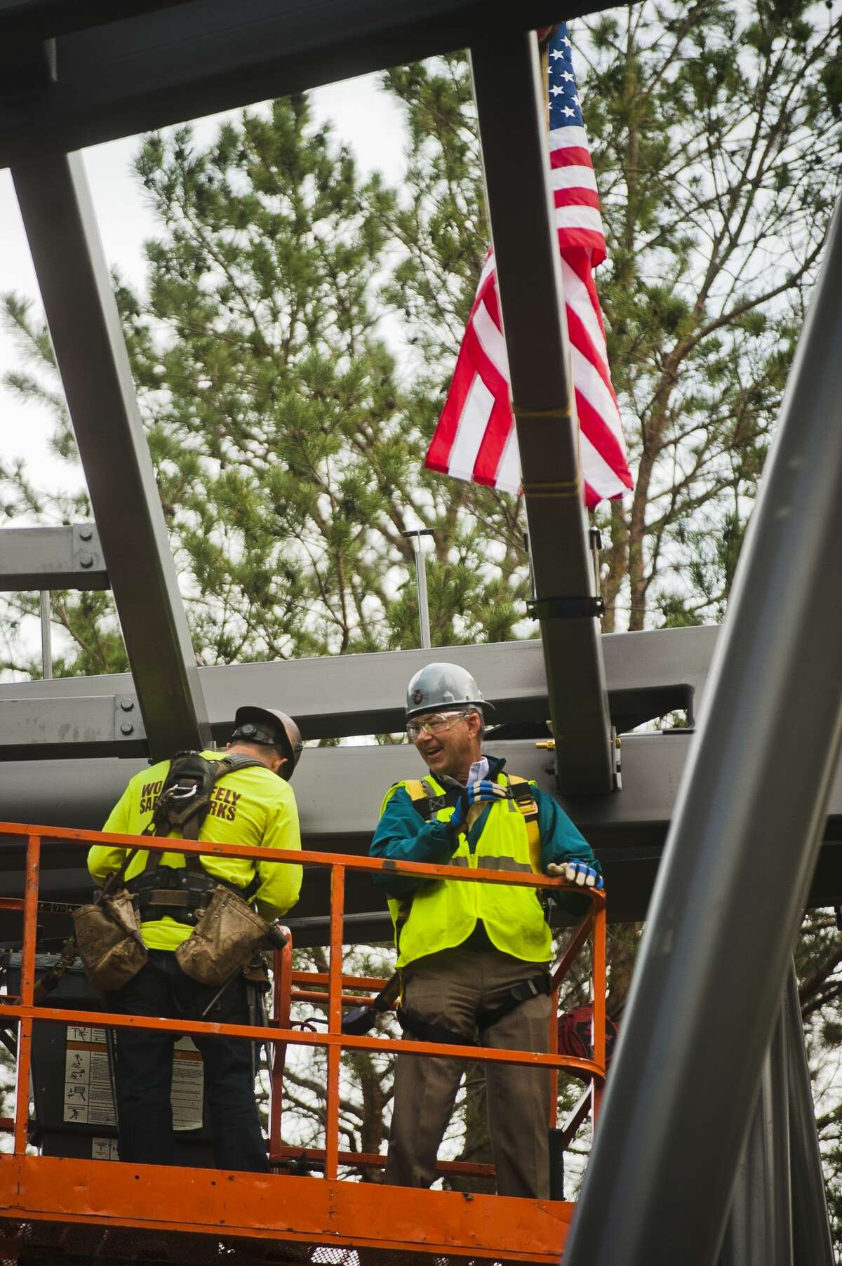 Mike Whiting Jr., President of The Herbert H. and Grace A. Dow Foundation, right, assists construction workers in placing the final support beam on the