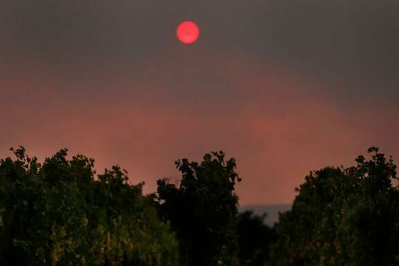 A red sun sets through a blanket of smoke over the vineyards off of Silverado Trail road Oct. 9, 2017 in Napa, Calif.