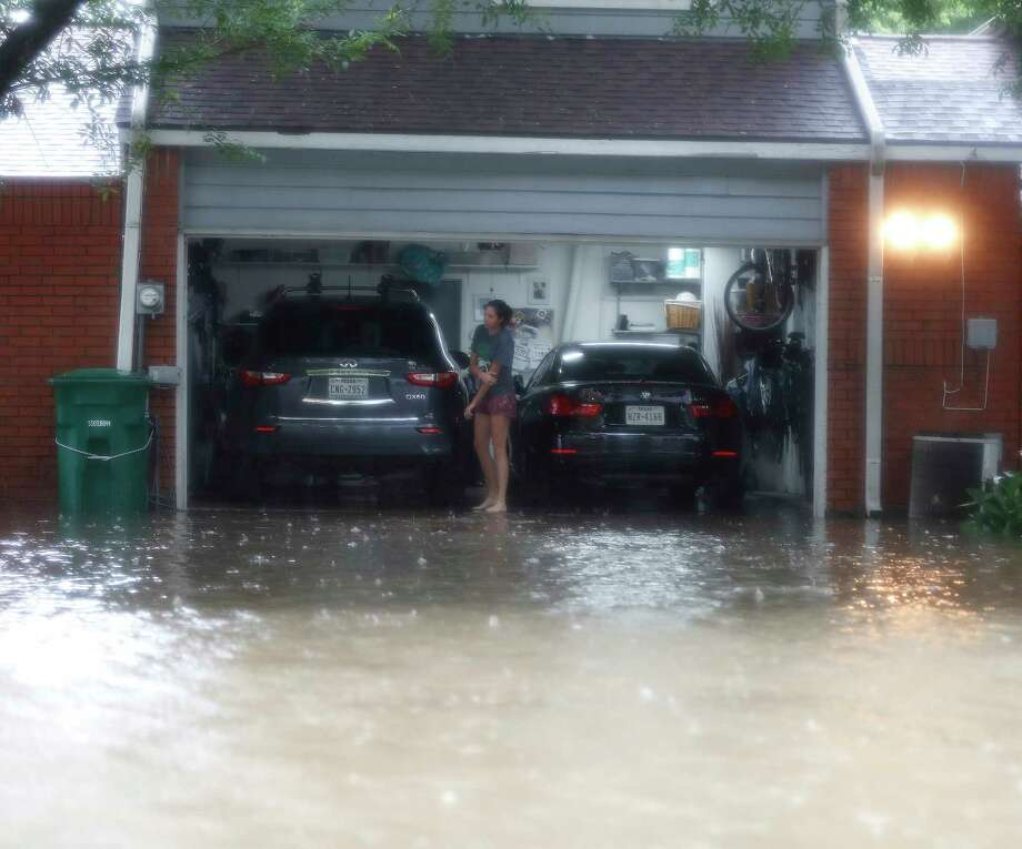 A woman stands in her garage with flood water up to the garage in the Heights, after heavy rain from Hurricane Harvey fell overnight,  Sunday, Aug. 27, in Houston. Photo: Karen Warren, Staff Photographer / @ 2017 Houston Chronicle