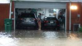 A woman stands in her garage with flood water up to the garage in the Heights, after heavy rain from Hurricane Harvey fell overnight,  Sunday, Aug. 27, in Houston.