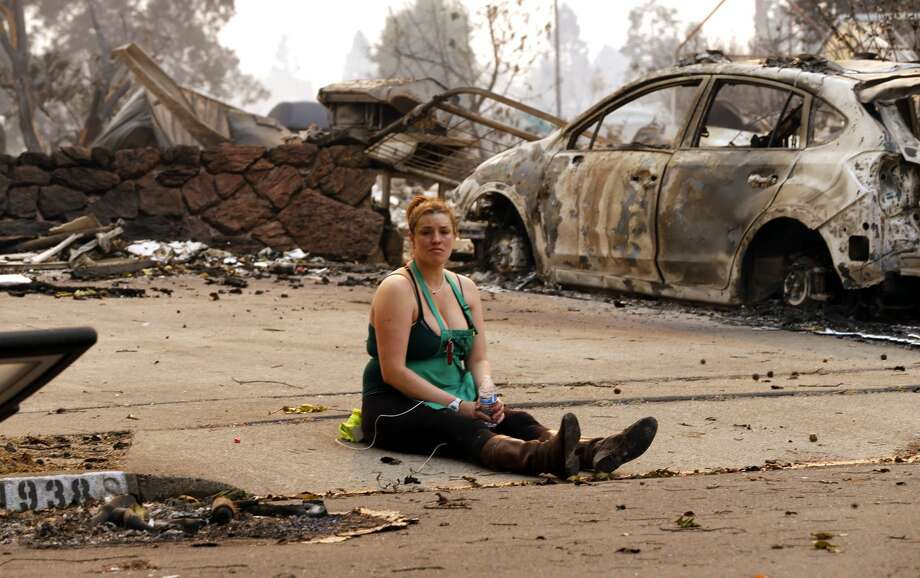 Nikki Albrecht takes a break in front of her mother's destroyed home at the scene of the Tubbs Fire in Santa Rosa, Ca., on Monday October 9, 2017. Massive wildfires ripped through Napa and Sonoma counties early Monday, destroying hundreds of homes and businesses on Monday October 9, 2017 Photo: Michael Macor/The Chronicle