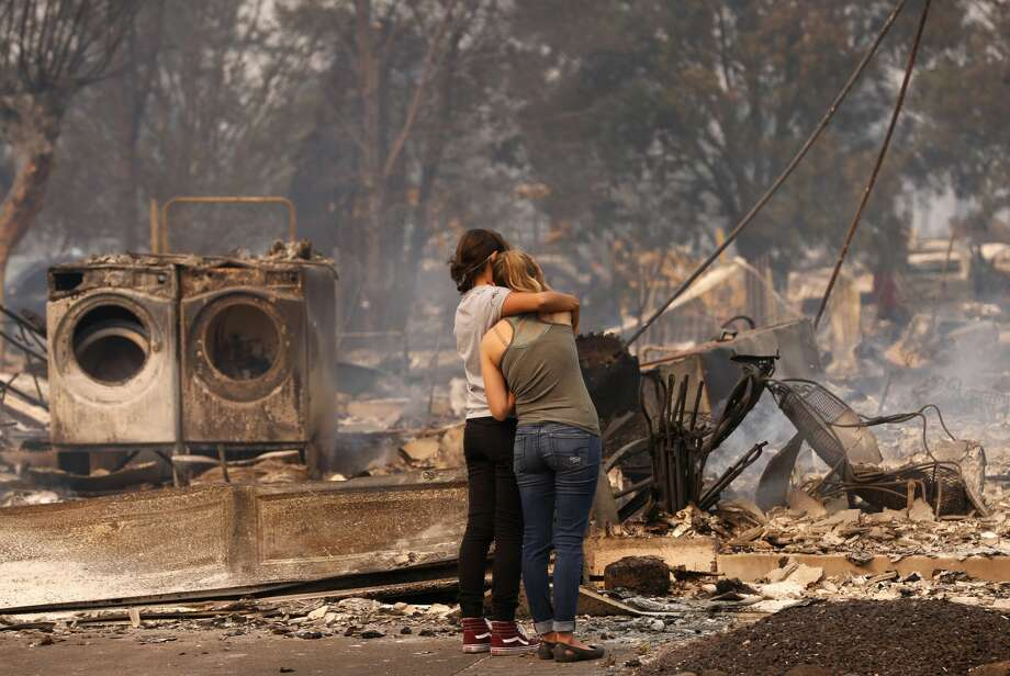 Steph Gediman, (left) comforts Brandi Burns in front of Burns' destroyed at the scene of the Tubbs Fire in Santa Rosa, Ca., on Monday October 9, 2017. Massive wildfires ripped through Napa and Sonoma counties early Monday, destroying hundreds of homes and businesses on Monday October 9, 2017 Photo: Michael Macor/The Chronicle