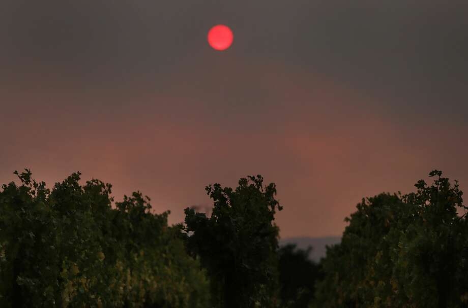 A red sun sets through a blanket of smoke over the vineyards off of Silverado Trail road Oct. 9, 2017 in Napa, Calif. A fire tore through the area on the evening of Oct. 8, destroying properties and vineyards. Photo: Leah Millis/The Chronicle