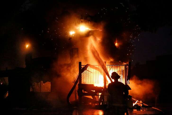 A firefighter with Cal Fire pours water onto the America's Best Value Inn along Cleveland Ave. which is a total loss in the fire, in Santa Rosa, Ca., on Monday October 9, 2017. Massive wildfires ripped through Napa and Sonoma counties early Monday, destroying hundreds of homes and businesses on Monday October 9, 2017