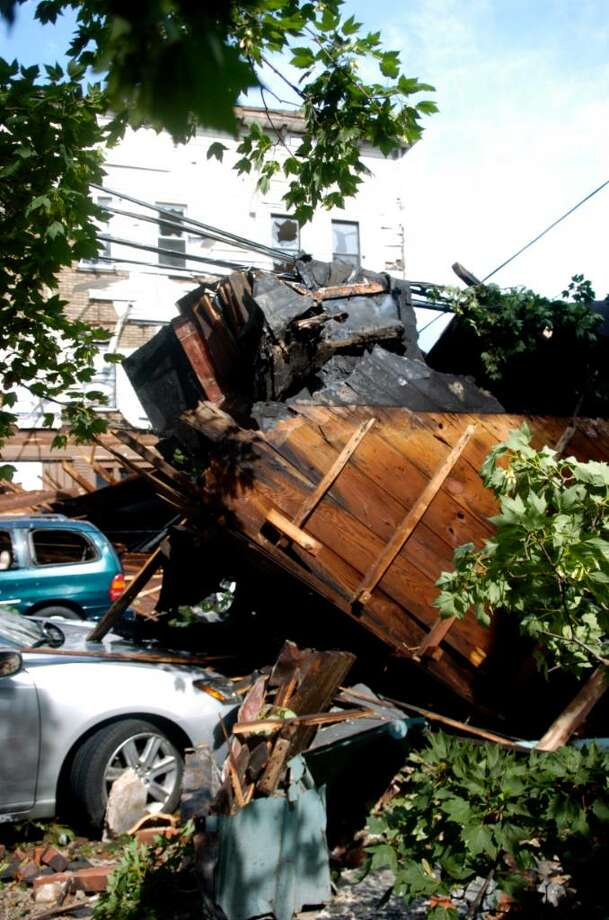 Pieces of the facade of a building on East Main Street in Bridgeport lay across cars and power lines after a storm tore through the area Thursday, June 24, 2010. Photo: Lindsay Niegelberg / Connecticut Post