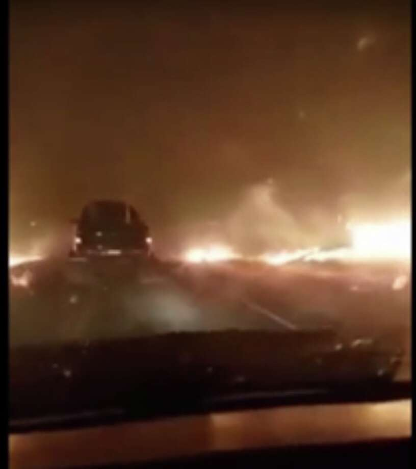 Stills from a video taken Sunday night show a couple fleeing the destruction of the Yuba County wildfire as it raged on both sides of the roadway. Photo: Storyful