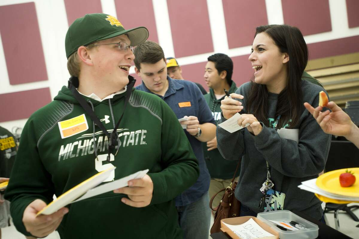 Logan Cummings, a member of the Dow High class of '16 and marching band alumnus, left, jokes around with Mackenna Greene, also a member of the class of '16 and the marching band, during the marching band's 50th reunion celebration before Dow's homecoming football game against Arthur Hill on Friday, Oct. 6, 2017. (Katy Kildee/kkildee@mdn.net)