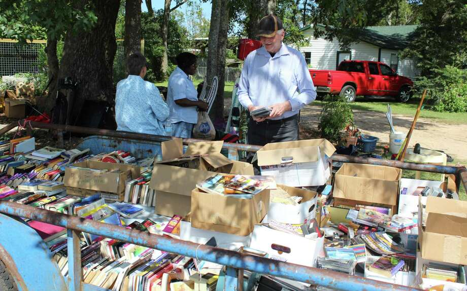 A trailer full of books and movies draws the attention of a group of customers at the Coldspring Library Garage Sale. Photo: Jacob McAdams