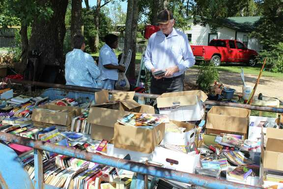 A trailer full of books and movies draws the attention of a group of customers at the Coldspring Library Garage Sale.