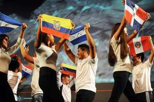 Westhill High School students walk across the stage with flags representing the diverse Hispanic population of the school during Westhill's Hispanic Heritage month celebration inside the school's auditorium in Stamford, Conn. on Tuesday, Oct. 10, 2017.