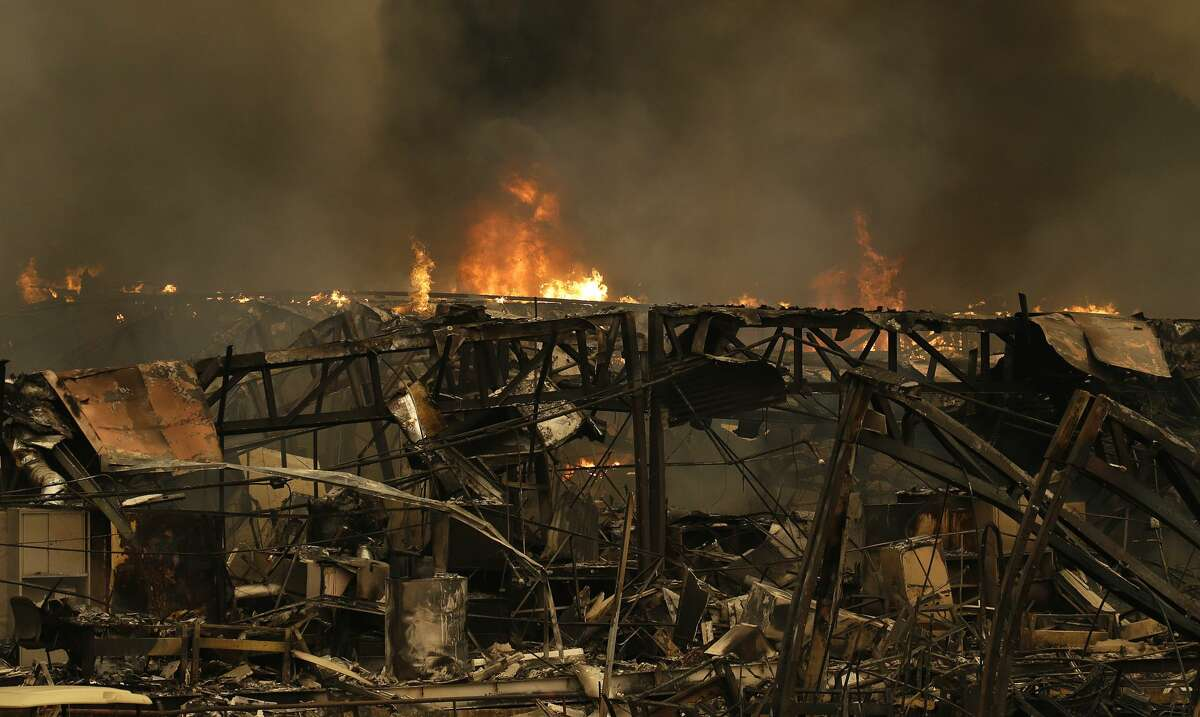 Fire continues to burn at Keysight Technologies Monday afternoon, Oct. 9, 2017, in Santa Rosa, Calif. Wildfires whipped by powerful winds swept through Northern California early Monday, sending residents on a headlong flight to safety through smoke and flames as homes burned.