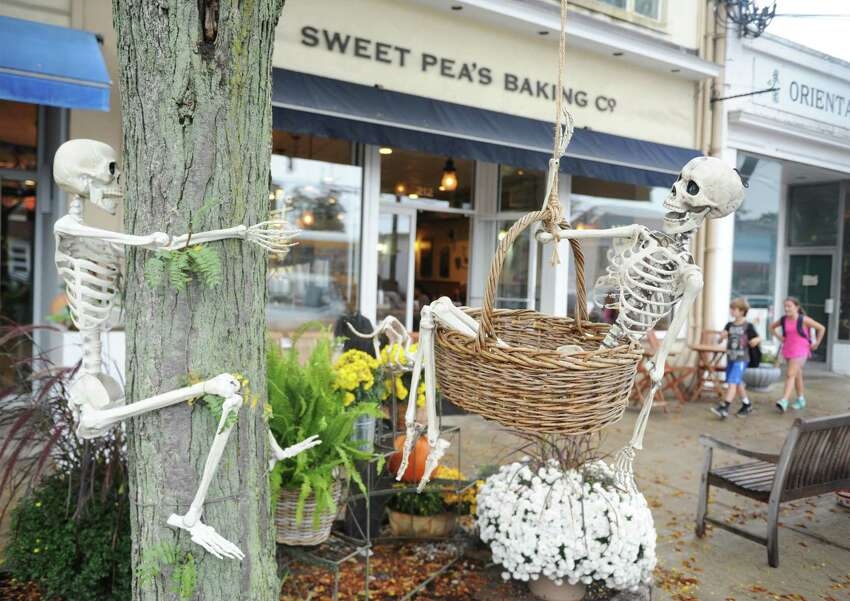 Spooky skeletons are displayed outside Sweet Pea's Baking Company and Something Special Flowers in downtown Old Greenwich, Conn. Monday, Oct. 9, 2017.