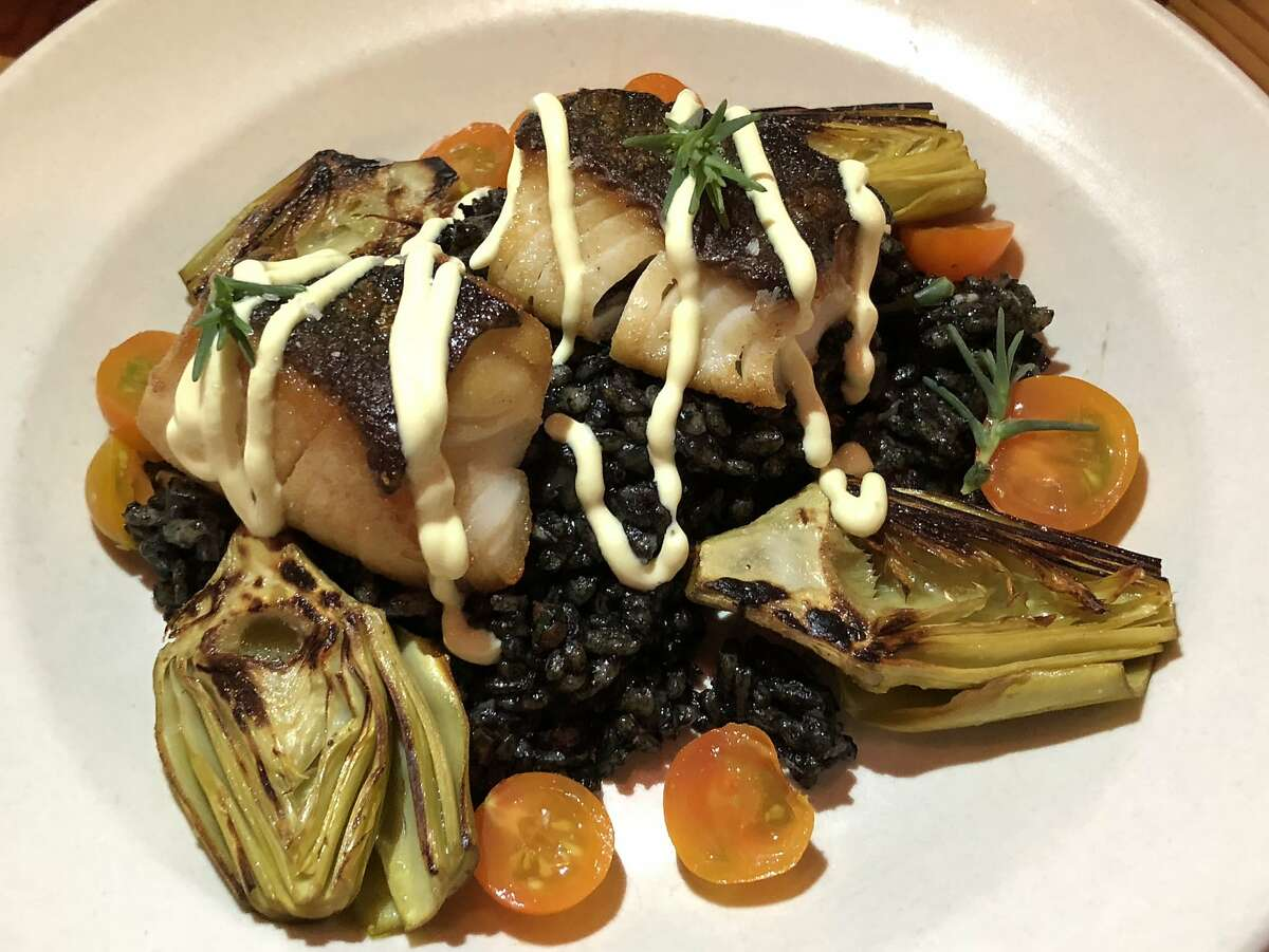 Cod on black rice with artichokes and tomatoes