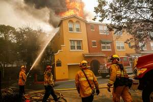 Firefighters work to contain the Tubbs fire at the Overlook apartment complex off of Bicentennial Way in Santa Rosa, Calif., on Monday, Oct. 9, 2017.