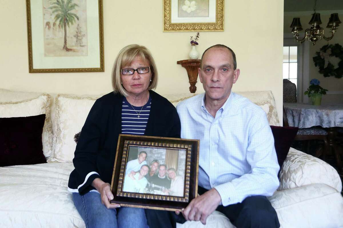 Linda and Richard Pape, parents of the late Dylan Pape, pose with a family picture at their home. Dylan was killed by SWAT officers at his home on March 21.