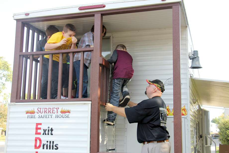 Students emerge from a fire house brought on Harbor Beach Community School grounds Tuesday by members of the local fire department. Firefighters taught students fire safety tips and discussed the proper protocols for handling a fire situation, if one were to ever occur. Photo: Bradley Massman/Huron Daily Tribune